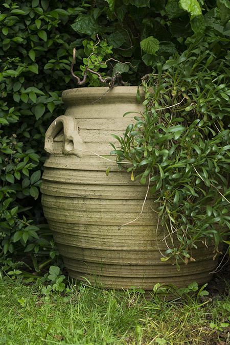Large partially hidden Greek style pot in the garden